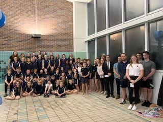 Memmber of the Rhyl Dolphins Swimming Club with representatives from the three charities