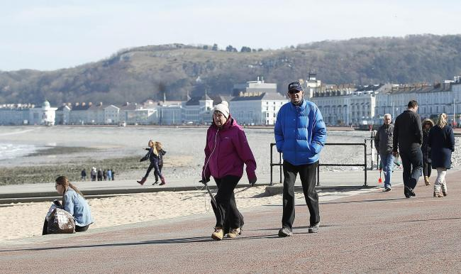 People walk along the promenade in Llandudno as the Government continues to advise the public to reduce social interaction due to the coronavirus outbreak Picture: Martin Ricketts / PA
