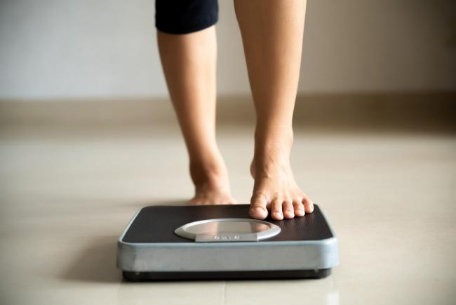 Generic photo of someone stepping on scales. Picture credit should read: iStock/PA.