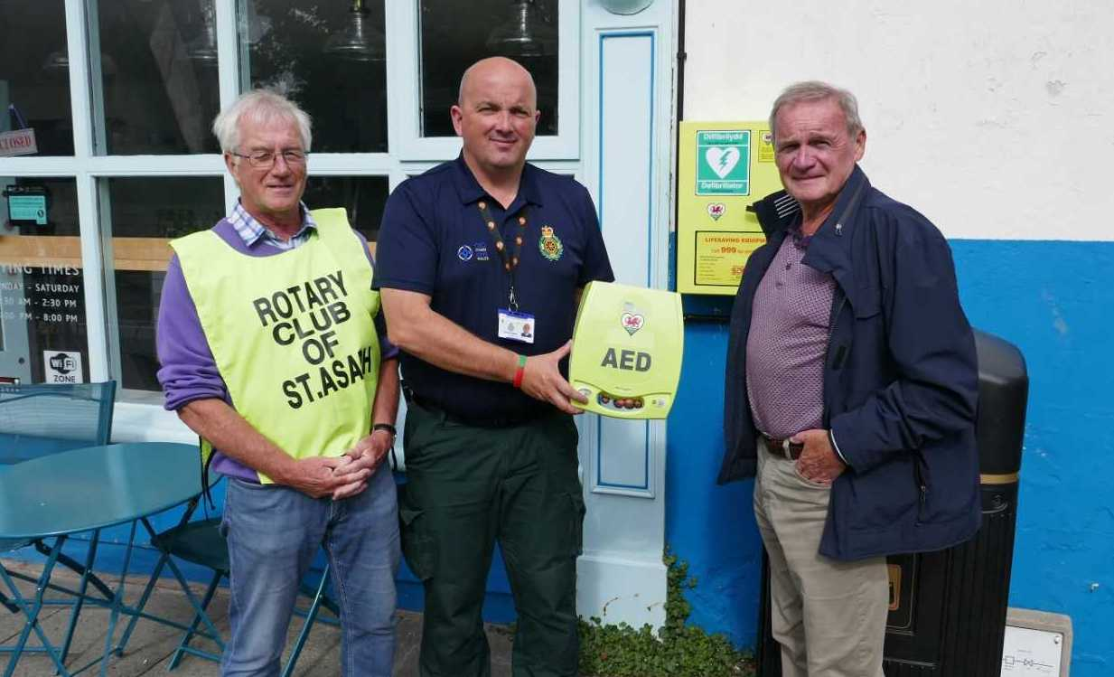 Past president Tom Yuille with Tomos Hughes, Welsh Ambulance Service and Colin Hardie, Mayor of St. Asaph, at the installation of the defibrillator