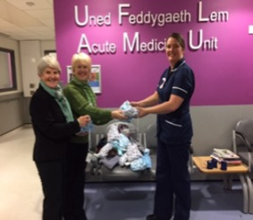Soroptimists Esther Roberts and Lesley  Roberts  presenting toiletries bags to Karen Paton, ward manager the of acute medical unit at Glan Clwyd Hospital