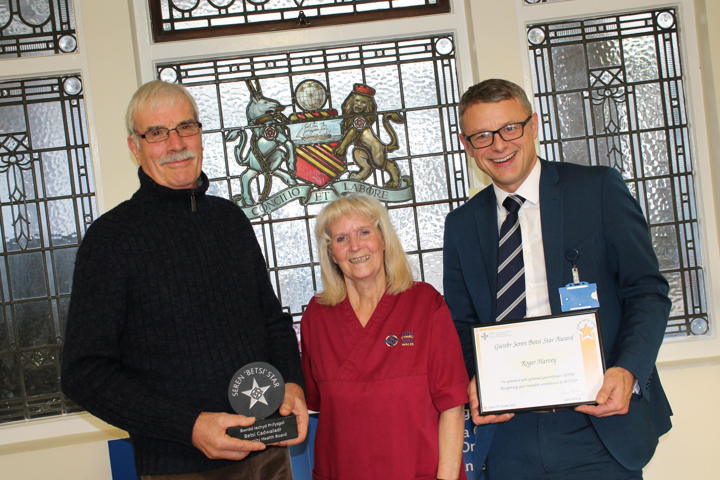 Roger Harvey receives his award from Gary Doherty, Chief Executive of Betsi Cadwaladr University Health Board. Also pictured is Domestic Assistant Angela Fortune