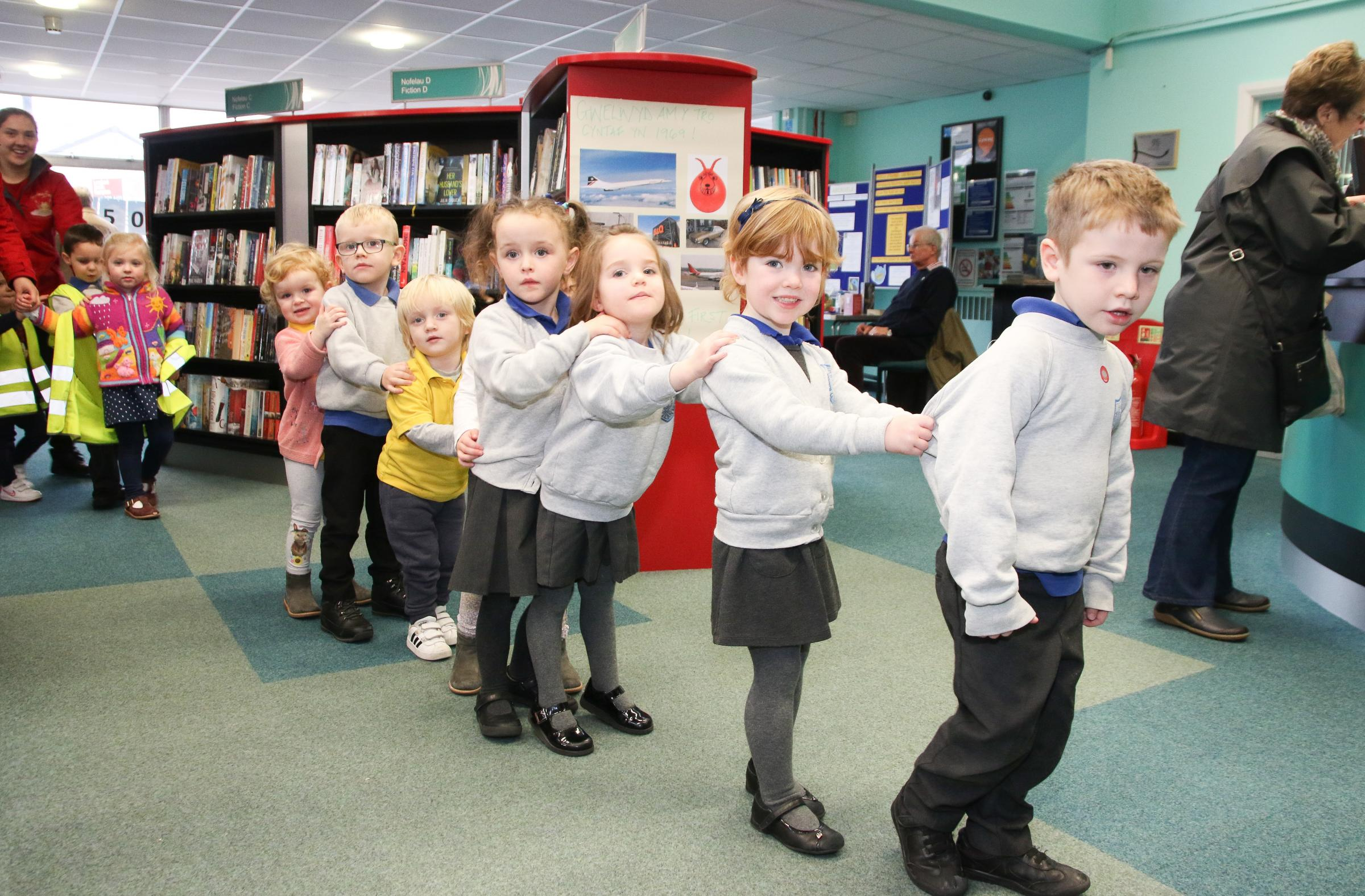 The Hungry Caterpillar was also published 50 years ago, and these children from Cylch Meithrin Abergele came to hear a reading from assistant librarian Judith Griffith and then formed a caterpillar to tour the library. KR100119c.