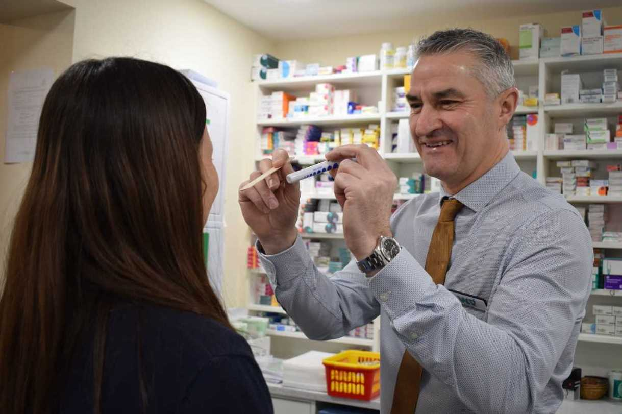Pharmacist Gerald Thomas performs the new, quick sore throat swab test on a patient