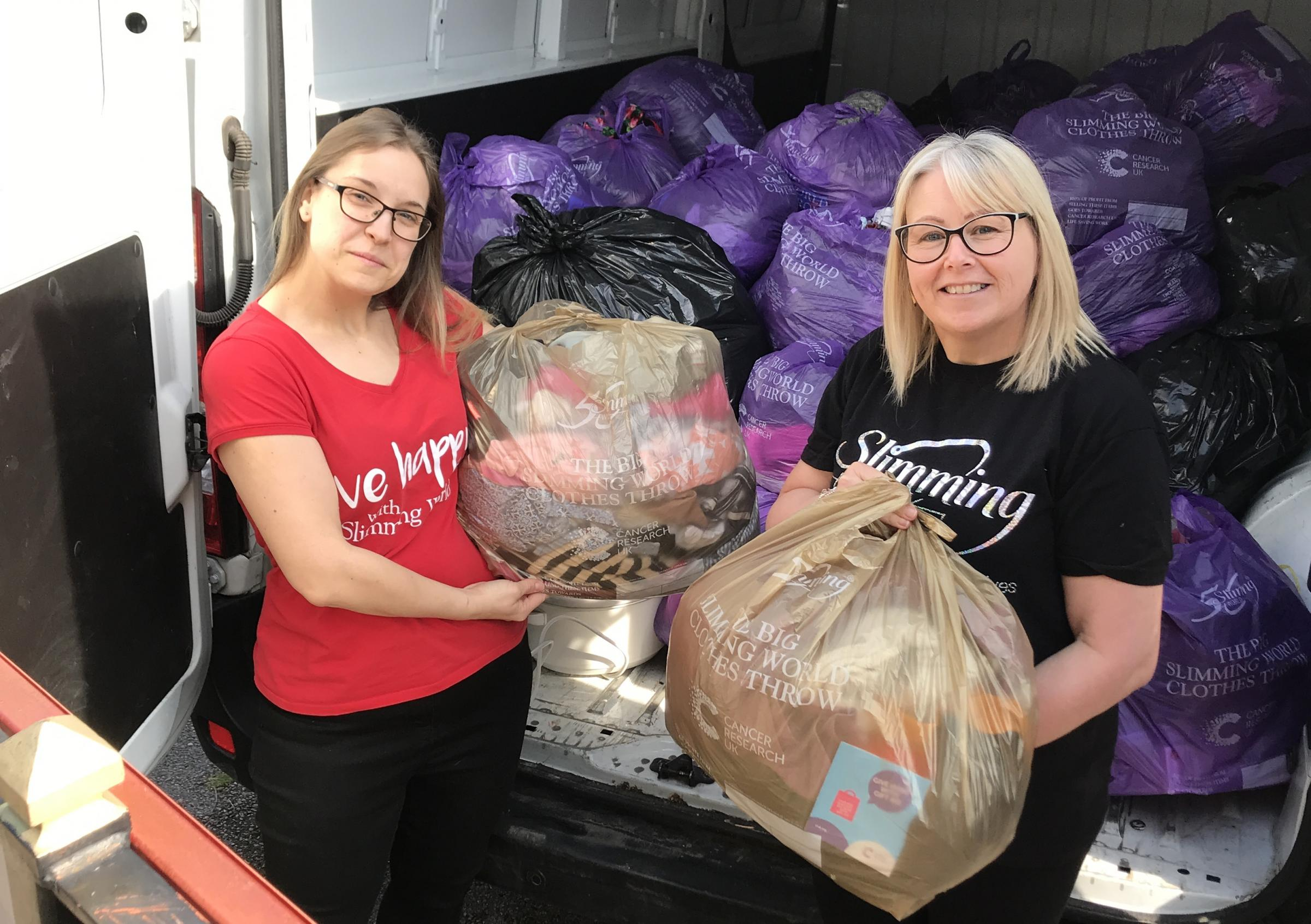 Tracy Cawthray (right) and Slimming World volunteer with the bags of now oversized clothes.