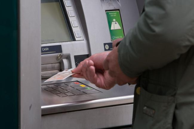 Image of person withdrawing money from an ATM. Picture: Aaron Chown/PA Wire