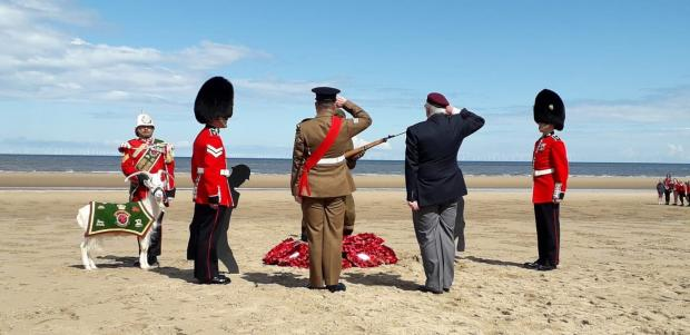 Rhyl Journal: Ex-servicemen salute the 'Tommy' memorial in memory of the fallen. Picture: Kerry Roberts